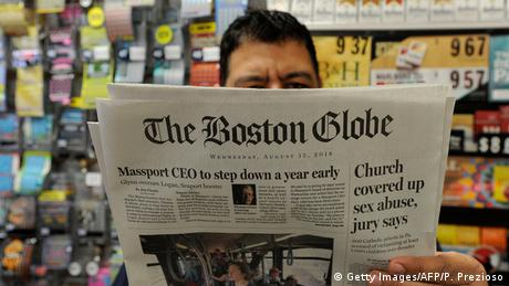 in a shop in Bosten, a man reads an 2018 issue of The Boston Globe newspaper with headline Chruch covered up sex abuse, jury says