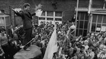 Lech Walesa, head of the striking workers delegation, stands on a make shift podium as he adresses stirking workers waving flowers after negotiations, August 26, 1980, and signing of the preliminary contract between the striking workers and the Polish government delegation, led by deputy Premier Mieczyslaw Jagielski, at the Lenin shipyard in Gdansk, Poland. Walesa holds the contract in his hand. (AP Photo/Reportagebild)