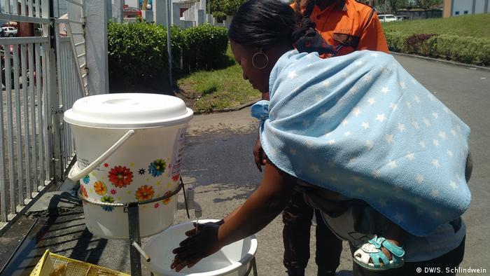 Mujer se lava las manos en la entrada de un hospital del Congo