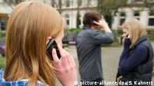 Schüler telefonieren am 22.04.2013 auf einem Schulhof in Braunschweig (Niedersachsen). Die Zehntklässler zweier Braunschweiger Schulen hatten für eine Woche freiwillig auf ihr Handy verzichtet. Foto: Sebastian Kahnert/dpa   Verwendung weltweit
