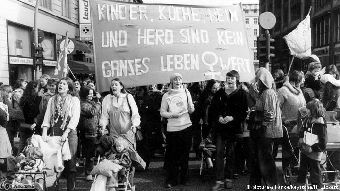 women marchin in protest with large banner in 1980