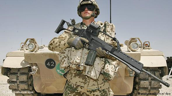A NATO soldier standing in front of a tank