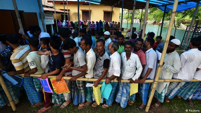 People wait in line in Assam state, India, to register as citizens