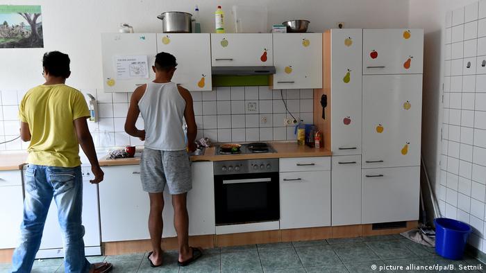 Dois jovens preparam sua comida num lar para refugiados em Brandemburgo
