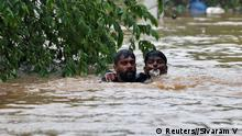 A man rescues a drowning man from a flooded area