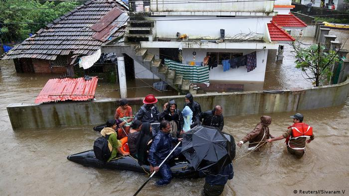 Rescue workers evacuate people from flooded areas
