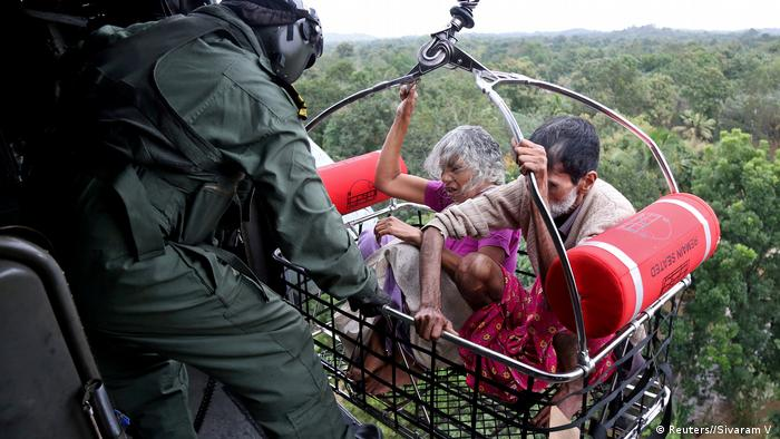 People are airlifted by Indian Navy soldiers during a rescue operation at a flooded area.