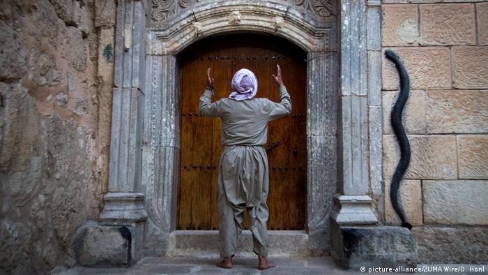 A Yazidi man prays at the door of the holy temple of Lalesh
