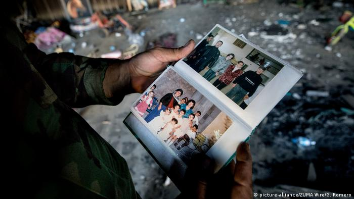 A man holds a photo showing members of a Yazidi family