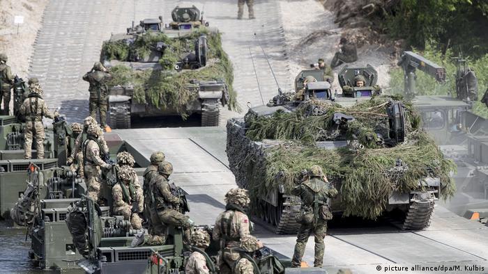Солдаты немецкого бундесвера в грузовиках и танки во время военных маневров НАТО