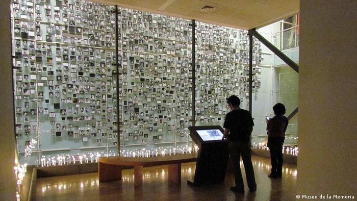 Pared con fotos y velas prendidas en el suelo del museo