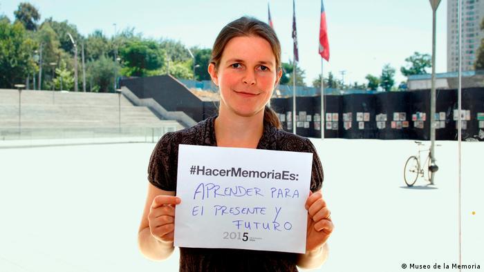 """Mujer en el exterior del museo con papel que dice #HacerMemoriaEs: """"Aprender para el presente y el futuro"""""""