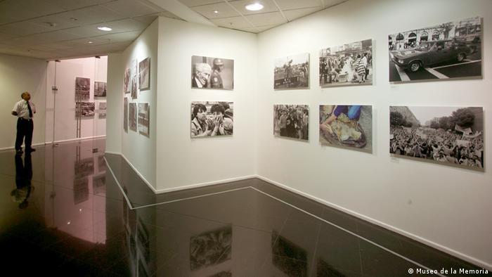 Sala de exposición fotográfica, con una persona al lado izquierdo.