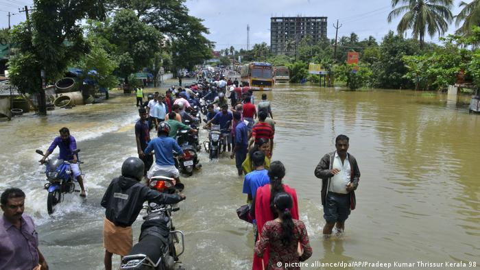 People make their way through flooded streets