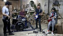In this July 20, 2018 photo, Afghan musicians Mohammad Rezai, left, Hakim Ebrahimi, second right, and Soraya Hosseini, right, members of the Arikayn rock band, along with Kourosh Ghasemi, an Iranian drummer, play music at a furniture workshop in Eslamshahr, outside Tehran, Iran. Like others in Iran's vibrant arts scene, Afghan musicians must contend with hard-liners who view Western culture as corrupt and object to women performing in public. (AP Photo/Ebrahim Noroozi) |