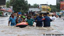 August 17, 2018 - Indian volunteers and rescue personal evacuate local residents in a boat in a residential area at Aluva in Ernakulam district, in the Indian state of Kerala on August 17, 2018. - The death toll from floods that have triggered landslides and sent torrents sweeping through villages in the Indian state of Kerala trebled on August 17 to 324, authorities said, amid warnings of worse weather to come. (Photo by - / AFP) (Photo credit should read -/AFP/Getty Images)
