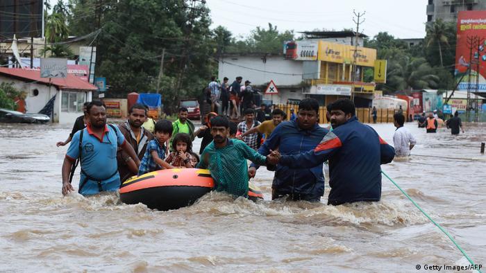 Equipes de resgate retiram vítimas da cheia usando bote de borracha
