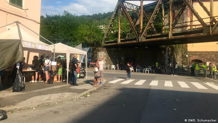 Tents on the sidewalk on a street near in Genova provides shade to boy scouts handing out water