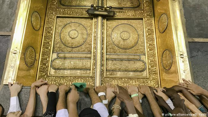 Pilgrims place their hands on the Kaaba during prayers.