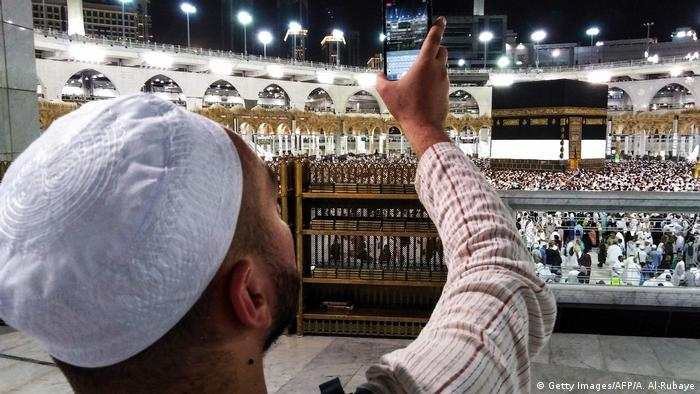 A pilgrim uses his smartphone to livestream worshippers circling the Kaaba at the Grand Mosque in Mecca.