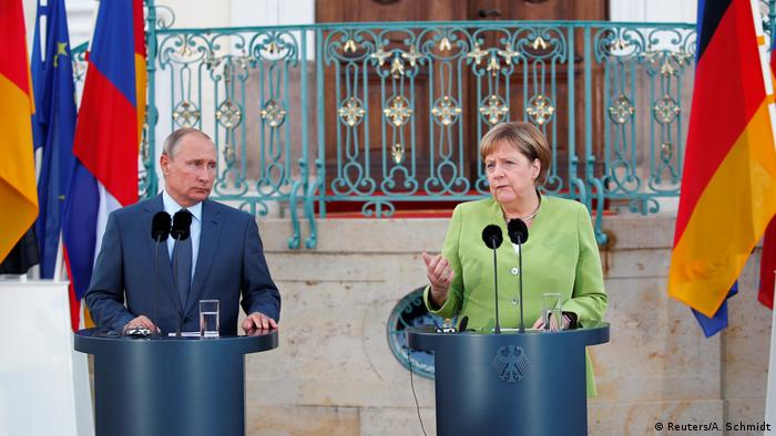 Merkel and Putin speaking to reporters before a private meeting (Reuters/A. Schmidt)