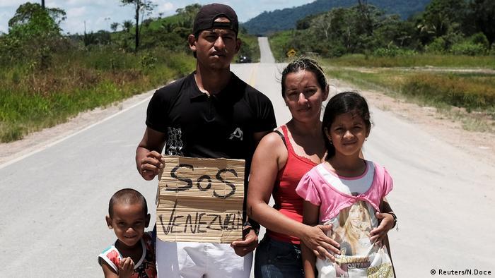 Brasilien, Venezolanische Familie aus dem Bundesstaat Aragua posieren für ein Foto, als sie versuchen, in Richtung Boa Vista Stadt trampen, nachdem sie Flüchtlingsstatus oder vorübergehenden Aufenthalt an der Grenzkontrolle von Pacaraima erhalten (Reuters/N.Doce)