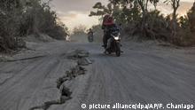 ARCHIV*** 11.08.2018, Indonesien, Gangga, Lombok: Eine Frau fährt mit ihrem Roller auf einer Straße, die vom Erdbeben aufgerissen wurde. Das schwere Erdbeben vor knapp einer Woche und Nachbeben auf der indonesischen Ferieninsel Lombok haben weit mehr Menschen das Leben gekostet als bisher vermutet. Die offizielle Zahl habe nun 387 Todesopfer erreicht, sagte ein Sprecher der nationalen Katastrophenschutzbehörde am 11.08. Foto: Fauzy Chaniago/AP/dpa +++ dpa-Bildfunk +++ |
