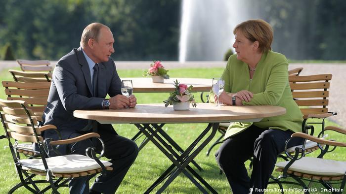 Putin e Merkel conversam ao ar livre, em uma mesa, nos jardins do Palácio de Meseberg