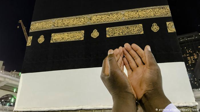 A pair of cupped-hands raised in prayer towards the Kaaba.