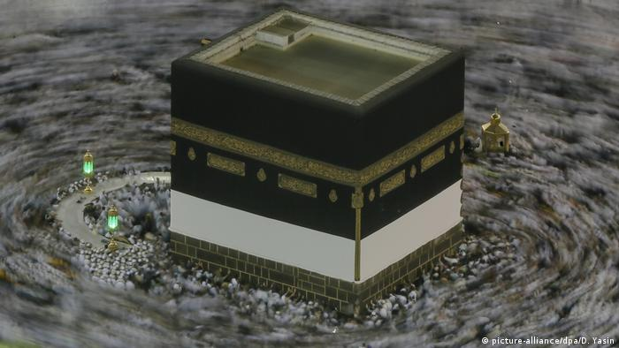 A slow shutter speed shows a blurry mass of pilgrims circling the cube-shaped Kaaba.