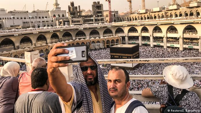 Two men pose for a selfie with the Kaaba in the background.