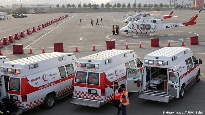Paramedics stand among their rescue vehicles - three ambulances and two helicopters.