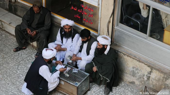 Afghan dealers count currency at a money market in Herat