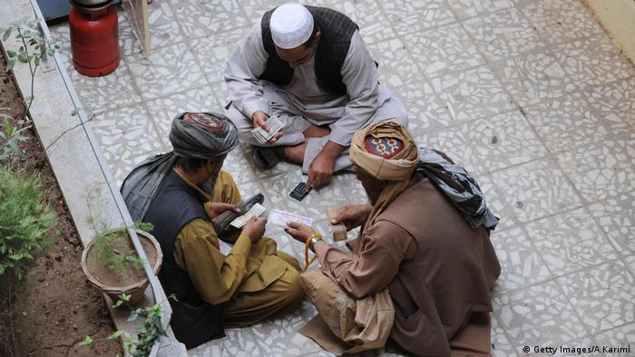 Afghan dealers exchange currency at a money market in Herat
