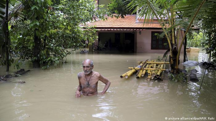 An Indian man stands up to his waist in brown water