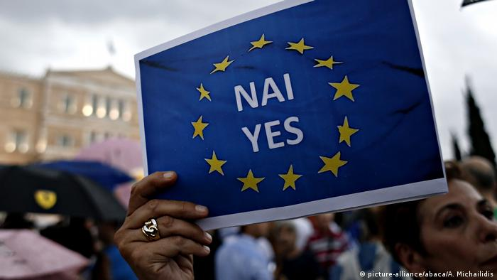 A woman holds a placard imploring Greeks to vote in favor of an EU bailout program