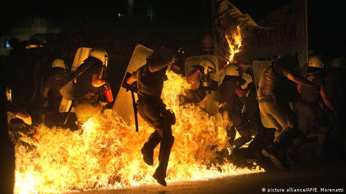 Anti-austerity protesters throw petrol bombs at riot police officers