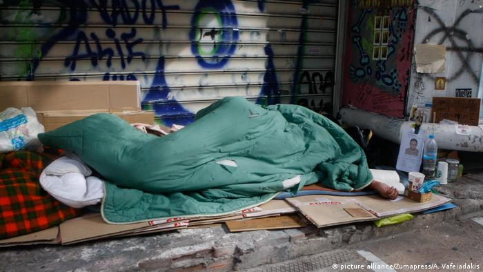 A homeless man sleeps on the streets of Athens