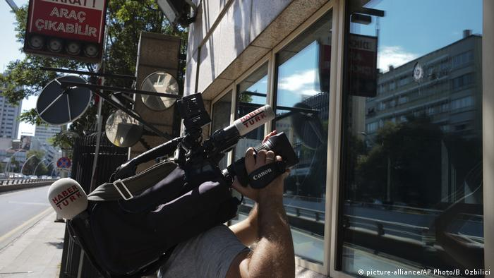 A news cameraman films the damage to a security booth by one of the shots fired at the US embassy