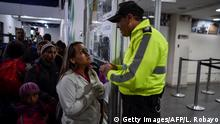 A Ecuadorean police officer explains the procedure to enter Ecuador to Venezuelan migrants outside the Ecuadoran Migration offices, at the Rumichaca International Bridge in Tulcan, Ecuador, on August 19, 2018, - Bogota said on August 17 it was worried that tightened Ecuadorean entry requirements for Venezuelans fleeing the economic and political crisis would leave thousands stranded in Colombia. Ecuador announced on Thursday that Venezuelans entering the country would need to show passports from Saturday onwards, a document many are not carrying. And Peru followed suit on Friday, announcing an identical measure due to begin a week later. (Photo by Luis ROBAYO / AFP) (Photo credit should read LUIS ROBAYO/AFP/Getty Images)