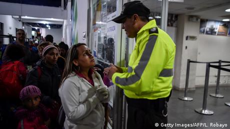 A man checks a passport of a woman on the border (Getty Images/AFP/L. Robayo)