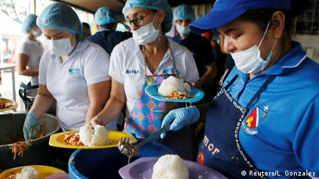 Women dish out food into plates in a refugee center (Reuters/L. Gonzales)
