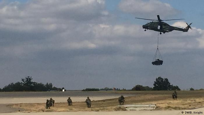 A helicopter flies a tank