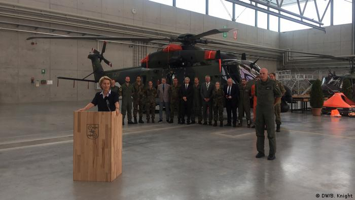 Ursula von der Leyen peaks in front of a helicopter and troops standing in a line (DW/B. Knight)