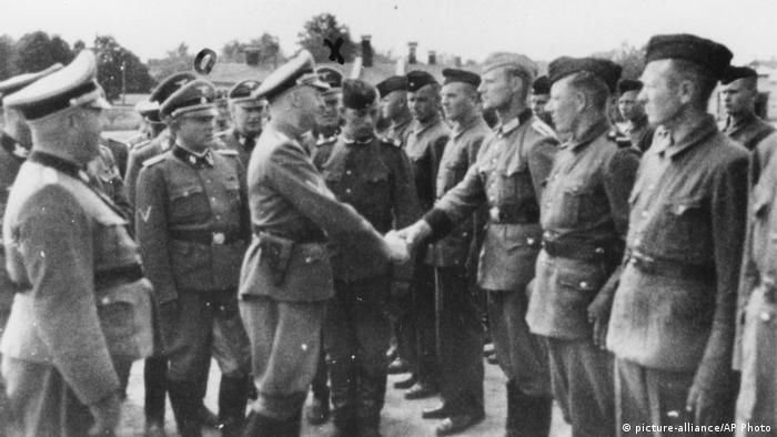 A Nazi shakes hands with guard recruits at the Trawniki camp
