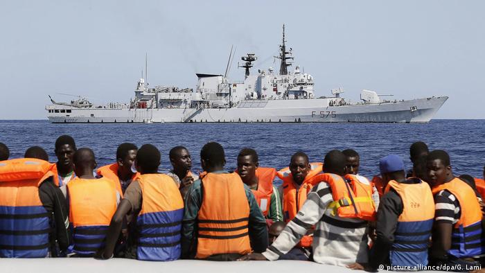 Sub-Saharan migrants (front) transported to an Italian Navy vessel (background) during a rescue operation in the southern Mediterranean Sea