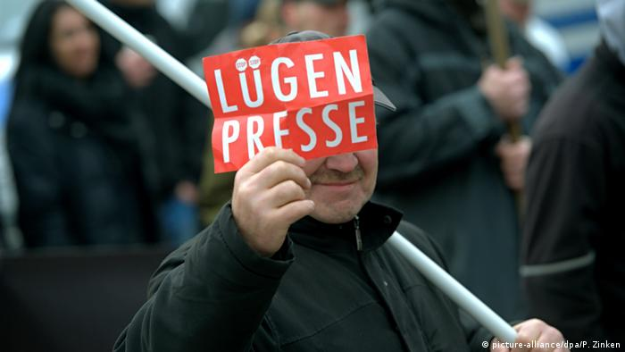 Man holds a sign that reads Lügenpresse or 'lying press'