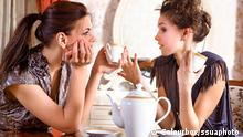 Two pretty girl-friends talk and drink tea in drawing room