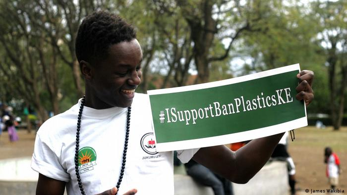 A young African man holds a sign that says ##ISupportBanPlasticsKE