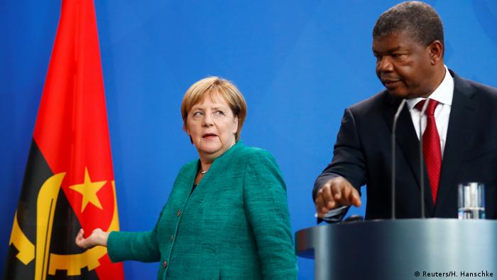 German Chancellor Angela Merkel (left) gestures to the Angolan flag beside a podium where Angolan President Joao Lourenco (right) is preparing to speak
